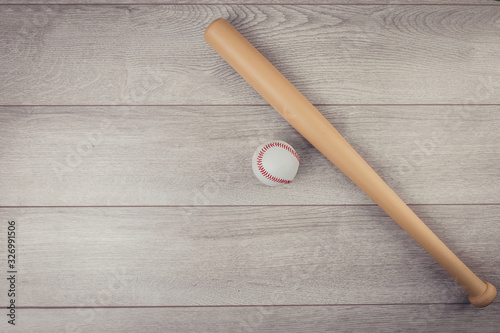 Wooden baseball bat and ball isolated on wooden background Wallpaper Mural