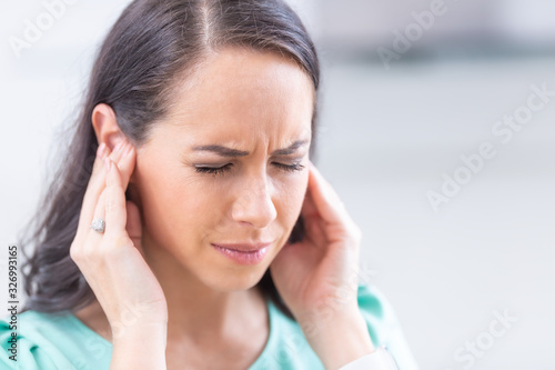 Fotografía Young woman have headache migraine stress or tinnitus - noise whistling in her e