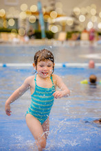 Portrait Of A Pretty Little Girl Playing In A Swimming Pool