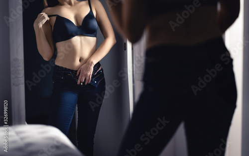 Sensual seductive sexy woman in the mirror in dark. Erotic woman wearing lingerie and underwear. Taking off bra in bedroom. Hot lady touching herself home at night. Sexual fantasy and desire.
