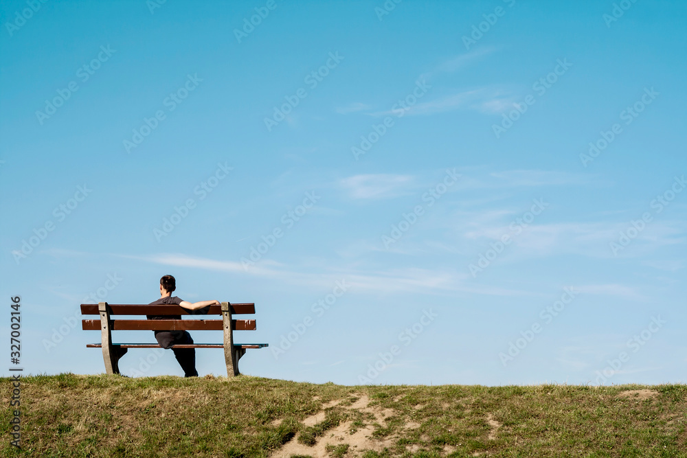 Fototapeta lonely man siting on a bench on an empty landscape