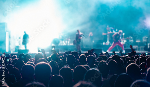 Music fans recording videos on phone in crowd on concert, rear back view of audience people using devices enjoy live music festival event shooting rock band stage on mobile device in blue lights Wallpaper Mural