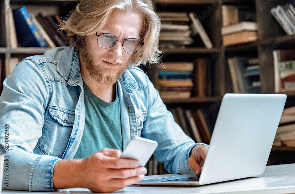 Fototapeta Confused perplexed man businessman student sit at office home library desk worried concerned frowning look at app modern broken stuck smartphone screen read bad news email sms message copy space.