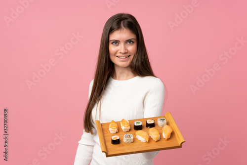 Fototapeta Young girl with sushi over isolated pink background with happy expression obraz