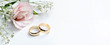 Leinwandbild Motiv Pink flowers and two golden wedding rings on white background.