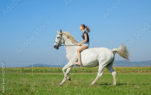 Photo Young woman running bareback with her beautiful white horse