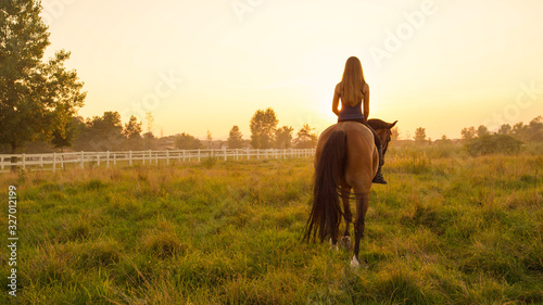 Pretty young blonde girl bareback riding towards rising sun Wallpaper Mural