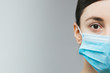 Woman with brown hair and a medical mask for protection again influenza. Copy space for your text. Woman with arms outstretched forward