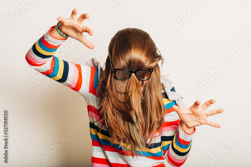 Fototapeta Studio portrait of young girl fooling around, hiding behind, hair, acting silly, time for haircut, hair completely covering the face with glasses over obraz