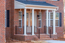 Portico Leading To The Entrance Of Brick Covered Building, With A Roof Structure Over A Walkway, Supported By White Round Columns On A New Single Family Home