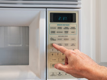 Using A Digital Keypad To Set The Microwave Oven Power Level And Microwaving Time For Cooking Or Reheating. Selecting Temperature And Cooking Timer Duration On Home Kitchen Appliance.