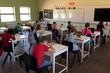 Group of schoolchildren sitting at desks working in an elementary school classroom
