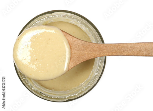 Fotografie, Obraz Sesame butter, paste tahini in wooden spoon and glass jar isolated on white back