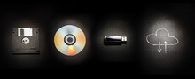Composition On A Black Background From A Floppy Disk, A Laser Disk, A USB Flash Drive And A Cloud Storage Symbol. The Evolution Of Storage Media.