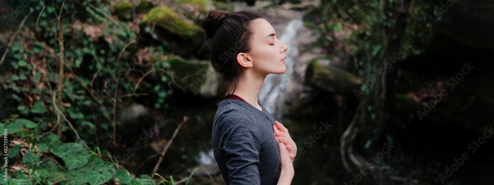 Fototapeta Young woman practicing breathing yoga pranayama outdoors in moss forest on background of waterfall. Unity with nature concept.