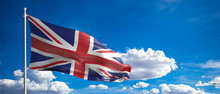 UK Flag Waving On Blue Sky Bac...