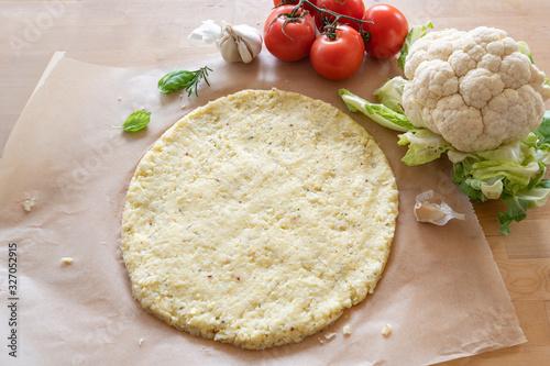 raw pizza base from shredded cauliflower on baking paper, healthy vegetable alte Fototapet