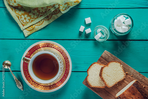 A tiffany color wooden table with a sliced cake on the cutting board, sugar cubes and two porcelain cups of tea Canvas Print