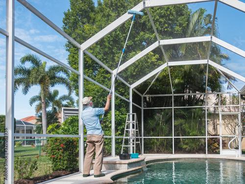 Fotografía Handyman cleaning outdoor pool cage enclosure with pole brush
