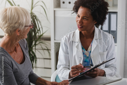 Fotomural A female doctor sits at her desk and chats to an elderly female patient while lo