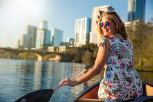 A Beautiful Woman In A Canoe Rowing On Colorado River Lake, Happy, Joyful In Austin Texas In America