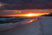 Colorful Dark Sunset In Santa Rosa Beach With Pensacola Coast In Florida Panhandle At Gulf Of Mexico Ocean Waves With Silhouette Of People