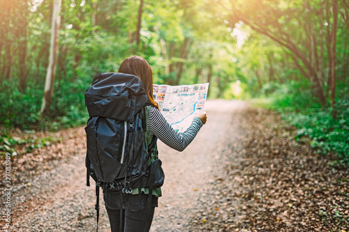 Traveling Happy Asian woman with backpack walking on path the tropical forest looking at the camera and map in green rainforests Canvas