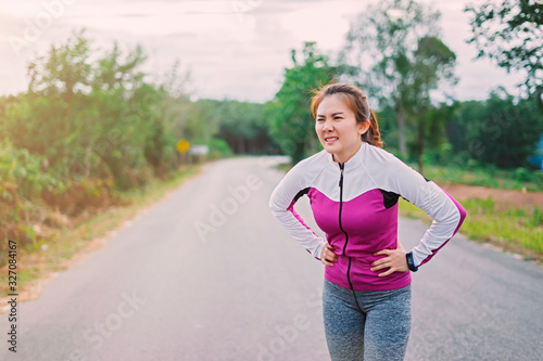 Photo Young fitness woman suffering from stomach pain, during running in Forest mounta