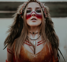 A Girl Dressed As A Native American With Roach And Streaks Of Red Paint On The Body Looking At The Camera
