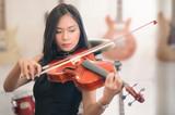 Beautiful asian woman playing violin.