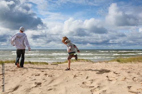 Brothers playing on the beach on a blustery spring day Wallpaper Mural