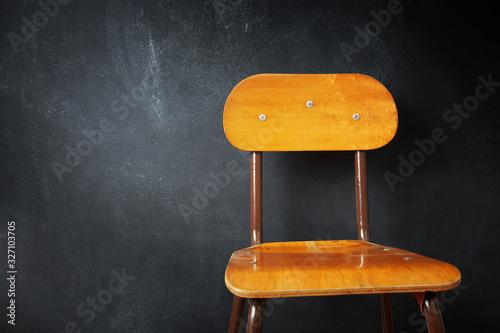 Canvas Print Empty wooden school chair against a black chalkboard in school