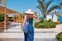 Woman In Hat And Blue Dress Go For A Walk In The Hotel Resort Near Swimming Pool With Beach Bag