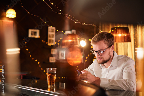 Photo people and technology concept - happy man with smartphone drinking beer and read