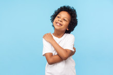 I Love Myself. Portrait Of Adorable Optimistic Little Boy With Curls Embracing Himself And Smiling, Self-confident Egoistic Child With Positive Self-esteem. Studio Shot Isolated On Blue Background