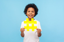 Charming Happy Cute Little Boy With Curly Hair In T-shirt Holding Big Yellow Hashtag Symbol And Smiling At Camera, Child Blogger Showing Hash Sign. Indoor Studio Shot Isolated On Blue Background