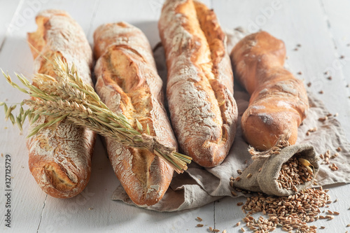 Photo Homemade golden baguettes with grains and ears of wheat