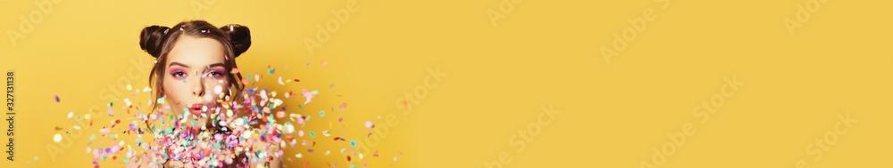 Fototapeta Beautiful woman blowing colorful confetti on yellow banner background