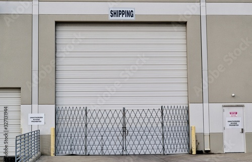 Fényképezés Single closed loading dock door with security gate and shipping sign above it