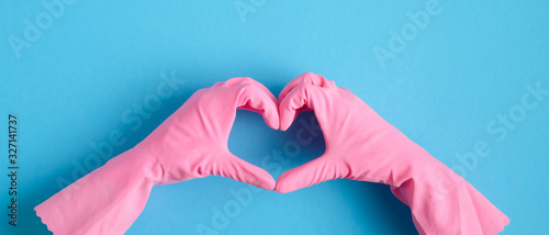 Fotografia Heart shaped hands in pink rubber gloves over blue background