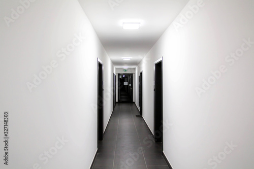 Stampa su Tela Simple clean newly built generic modern new real estate block of flats interior, long white corridor with black doors, perspective