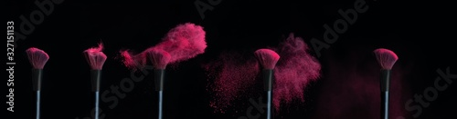 Photo Five make-up brushes with sequence of pink powder explosions on black background