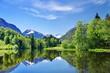 Bergsee im Frühling in den Alpen mit Gipfel und Schnee