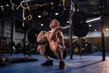 Muscular Male Athlete Squattin...