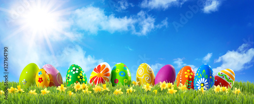 Fototapeta Colorful Easter eggs on green grass with spring flowers obraz