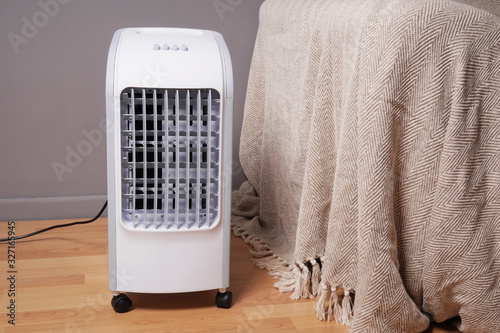 Obraz portable air cooler and humidifier on casters in domestic living room to improve indoor clmate - fototapety do salonu