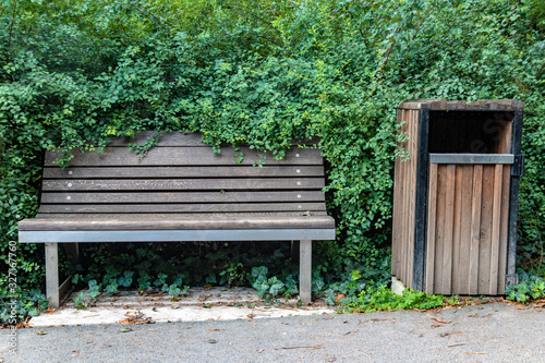 Photo An empty wooden bench with a waste bin beside way with the green bush around