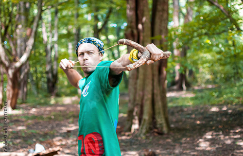 Valokuvatapetti A young man in a green T-shirt and bandana shoots from a large wooden slingshot