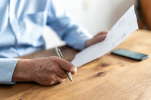 Elderly Man Reading A Letter From The Tax Authorities.