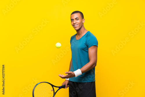 Afro American tennis player man over isolated yellow background Wallpaper Mural